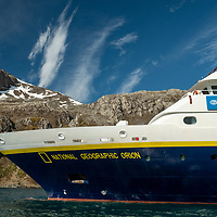 The National Geographic Orion ship anchored at Elsehul, a bay on the northwest coast of South Georgia Island, on a sunny day.
