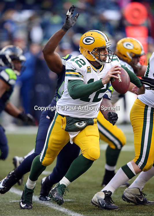 Green Bay Packers quarterback Aaron Rodgers (12) tries to run away from pressure from Seattle Seahawks defensive end Cliff Avril (56) who sacks Rodgers for a 7 yard loss and forces a punt during the NFL week 20 NFC Championship football game against the Seattle Seahawks on Sunday, Jan. 18, 2015 in Seattle. The Seahawks won the game 28-22 in overtime. ©Paul Anthony Spinelli