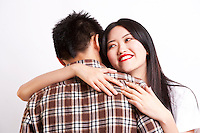 Beautiful young woman embracing man against white background