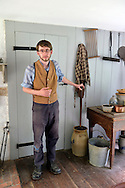Old Bethpage, New York, USA. August 30, 2015. Matt, a seasonal staff member wearing traditional style American clothing, shows a large butter churn during a tour of the Powell House during the Old Time Music Weekend at Old Bethpage Village Restoration. The house was built in 1750 and is restored to its expanded 1855 size, and is the only building standing on its original location in the village.