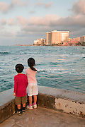 A young boy and girl looking at Waikiki at sunrise.