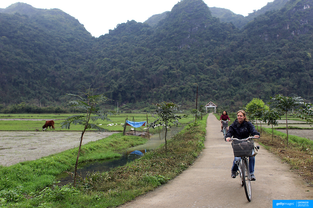 Tourists cycling on Cat Ba Island, the largest island in Ha Long Bay, Vietnam. The bay consists of a dense cluster of 1,969 limestone monolithic islands. Ha Long Bay, is a UNESCO World Heritage Site, and a popular tourist destination. Ha Long, Bay, Vietnam. 11th March 2012. Photo Tim Clayton