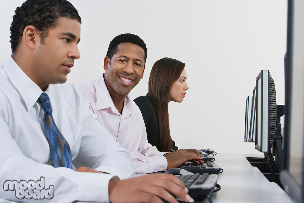 Three business people using computers in office