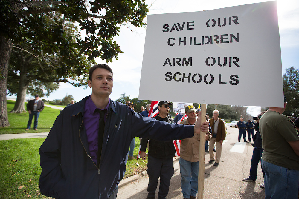 """January 18, Baton Rouge ,Ben Ernst  at a pro-gun rally organized by """"Guns across America"""" on """"Gun Appreciation Day"""", holds a sign with a message, """"Protect our children"""".After the massacre at  a school in Sandy Hook, Connecticut , the debate over gun control in America became a key political issue."""