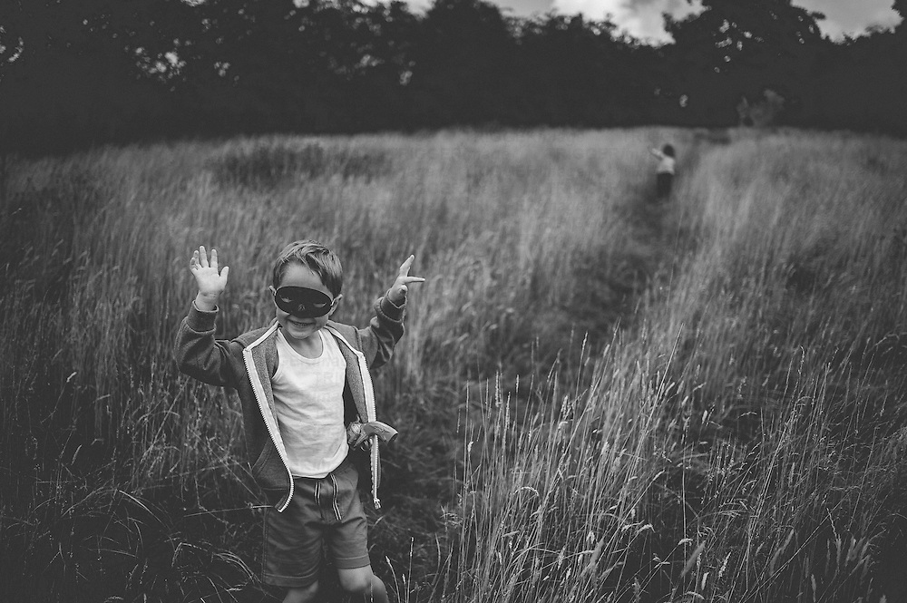 A boy aged 5-10 years old with arms raised standing in a field with long grass in summer wearing a mask smiling with a toy gun in his shorts