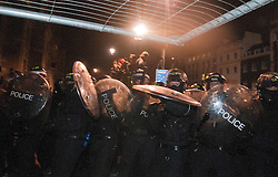 © under license to London News Pictures.  09/12/2010. Students thow a metal gate at police in Parliament Square, London, in an attempt to stop their line advancing. Photo credit should read Michael Graae/London News Pictures