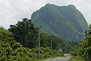 A large mountain formation called mogote overlooks a road near Vinales, Cuba.