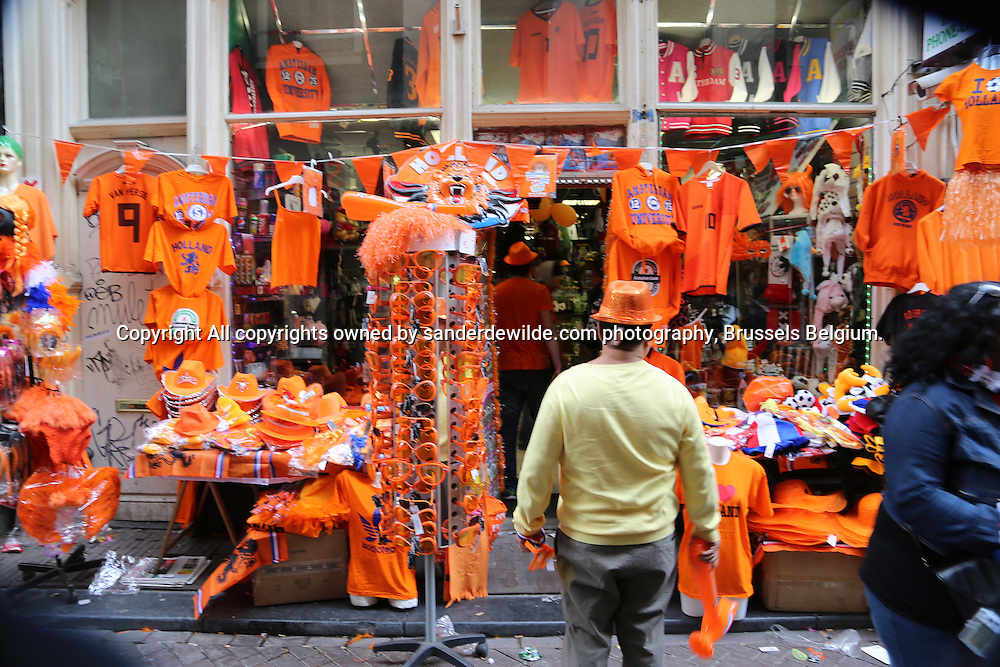 30th April 2013 Amsterdam, Netherlands. Queen Beatrix' abdication day, where her son Prince Willem-Alexander became King of the Netherlands. A man looks at his totally orange souvenirs-shop