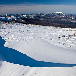 Wind scoured snow leads to a view of Mount Lafayette from Mount Clay in New Hampshire's White Mountains.