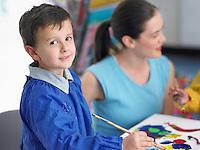 Art teacher squatting next to boy painting in art class