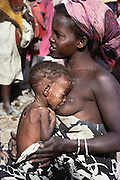 A mother nursing her sick child with other refugees in a camp near Merca, 100 km. south of Mogadishu, the war-torn capital of Somalia. March 1992.