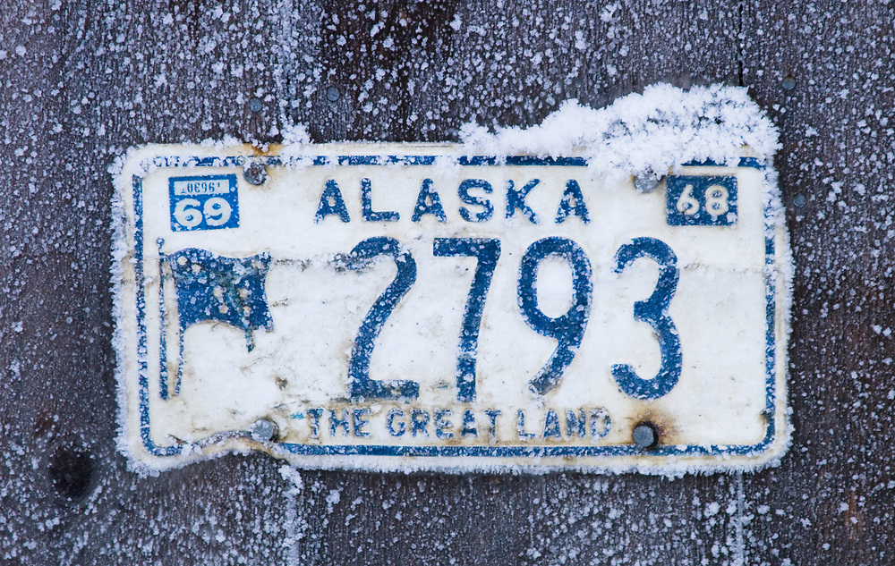 A blue and white Alaska license plate from 1968 is covered in ice and frost.