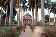 Women walking in front of  the tomb of Muhammad Shah in Lodi Gardens in New Delhi, India.