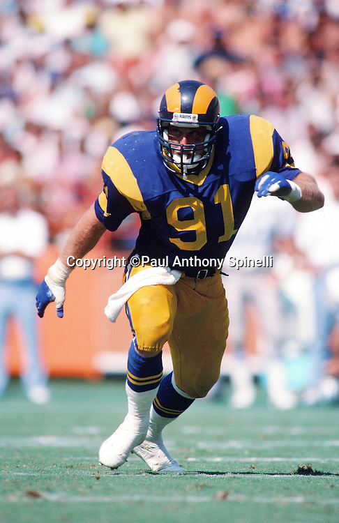 Los Angeles Rams linebacker Kevin Greene (91) chases the action during the NFL football game against the Detroit Lions on Sept. 11, 1988 in Anaheim, Calif. The Rams won the game 17-10. (©Paul Anthony Spinelli)