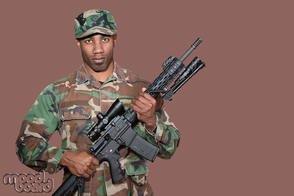 Portrait of African American US Marine Corps soldier holding M4 assault rifle over brown background