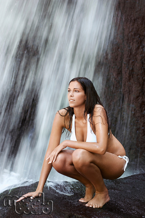 Young woman in bikini crouching by waterfall full length