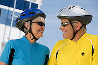 Senior couple wearing cycling helmets looking in eyes