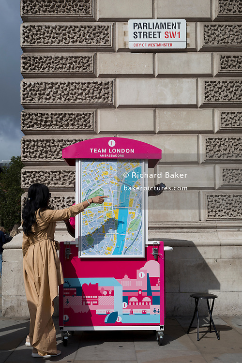 Visitors stop by a tourist information point for directions across the capital, on Parliament Square in Westminster, on 19th August 2019, in London, England.