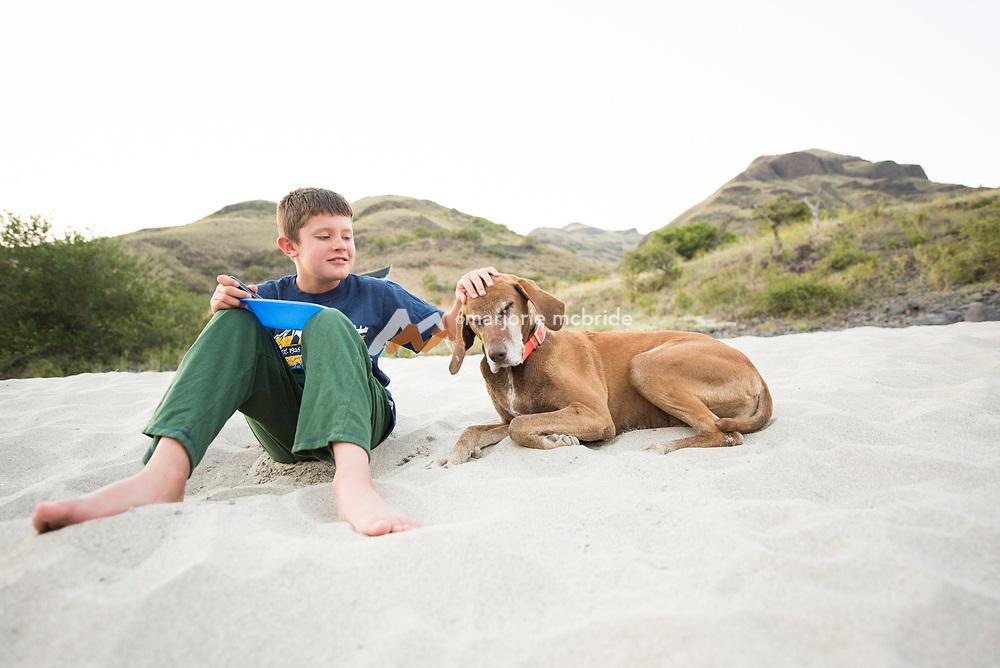 Little boy pets his dog on sandy beach at camp while rafting the Main Lower Salmon River, Hammer Creek to Hellar Bar, Idaho. MR