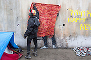 FRANCE, Calais: 18 December 2015 A refugee from Sudan prepares to unveil the Banksy painting of Steve Jobs in the refugee camp known as 'The Jungle'. He charges €1 to take a picture of the art work. The camp in Calais is now believed to hold 7,000 refugees, who are all trying to prepare for the cold winter months ahead.<br /> Rick Findler / Story Picture Agency