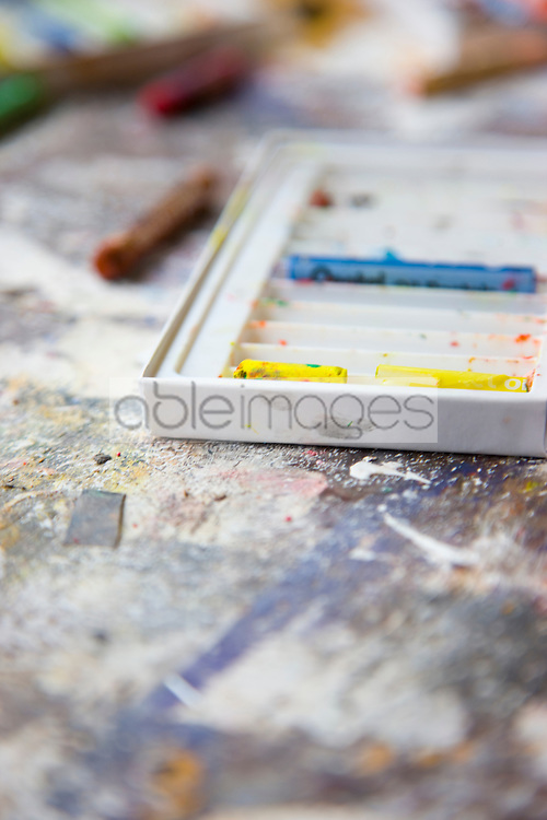 Close up of a messy art studio table with pencils and crayons