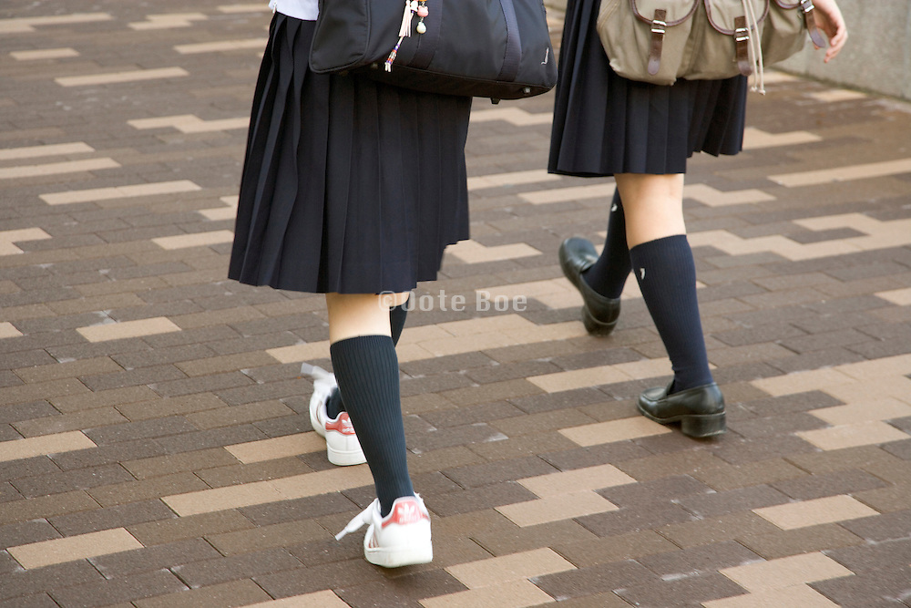 two Japanese students in uniform walking in unison
