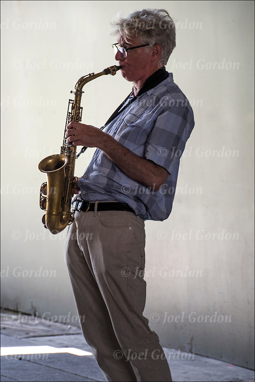 Street musician playing the saxophone<br /> <br /> The saxophone is a family of woodwind instruments. Saxophones are usually made of brass and played with a single-reed mouthpiece similar to that of the clarinet.