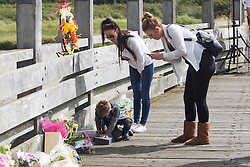 © Licensed to London News Pictures. 22/08/2016. Shoreham-by-Sea, UK. Georgia, Daniele Polito his son lays flowers to remember his father at the one year anniversary of the Shoreham Airshow Plane crash. 11 victims died when a Hunter Hawker Jet crashed during the 2015 Shoreham Airshow. Photo credit: Hugo Michiels/LNP