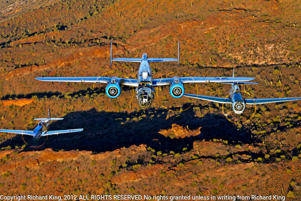 "An air to air color photographic image of three classic World War II 'planes (B-25 Mitchell ""Maid in the Shade"", P-51 Mustang ""Cripes A' Mighty"" and a TBM-3 Avenger) flying over Red Mountains in the Arizona desert"