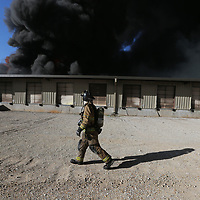A fireman walks past the loading docks to survey for far the fire has spread inside American Furniture iin Ecru Friday morning.