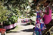 Une fille vêtue au couleur du clan de la femme est assise dans un arbre face à l'entrée de la tribu, marquée par un portique végétal décoré d'étoffes roses. – Mariage Kanak  - Tribu de Méhoué, Canala – Nouvelle Calédonie – Septembre 2013