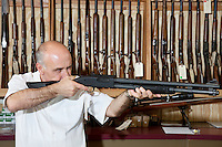 Mature gun shop merchant with rifle aiming