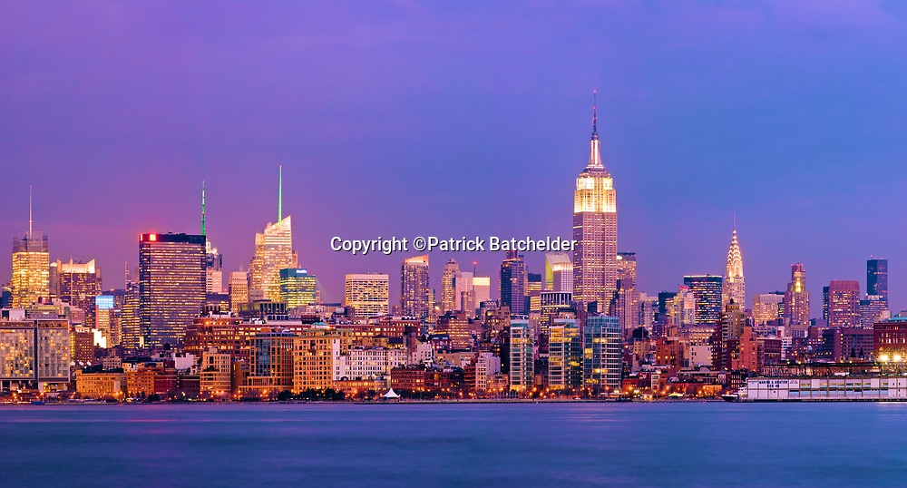 Panoramic skyline view of New York City, Manhattan at twilight, featuring, from left, the New York Times Building, One Bryant Park, the Empire State Building and the Chrysler Building, as seen from across the Hudson River.