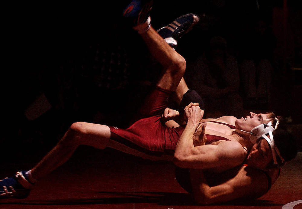 JEROME A. POLLOS/Press..North Idaho College's Jeff Hedges, tries to roll out on Johnny Rojas from Lassen College during the 125-pound weight class Thursday night. Hedges defeated Rojas 12-11 to help push the Cardinals team score to 41-6 against the Cougars.