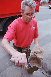 Builder using mortar; repointing trowel and mortar board to mend stone wall,