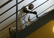 A painter and decorator varnishing each stair on a staircase inside the new East London Childcare Institute, Stratford, London.