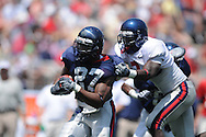Blue team running back Enrique Davis (27) is tackled by Red team defender Dele Junaid in Mississippi's Grove Bowl in Oxford, Miss. on Saturday, April 17, 2010. The play was called back because of penalty.