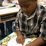 Elementary 3rd grade African American male student reading out loud sitting at their tables in Middleton-Burney Elementary Crescent City FL