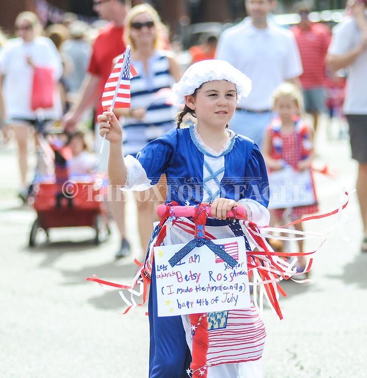 Ava Taylor Walker is dressed as Betsy Ross as she rides a scooter in a 4th of July parade in Oxford, Miss. on Monday, July 4, 2016. (Bruce Newman, Oxford Eagle via AP)