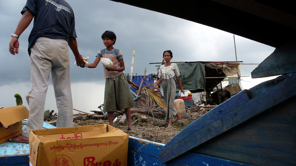 Burmese people from Rangoon distributing food to a mother and daughter living in a shelter in the aftermath of Cyclone Nargis near Pyapon. The woman lost her husband and three of her children in the cyclone. Their home has also been destroyed.