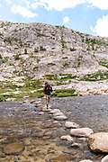 A teenage backpacker crosses Evolution Lake Inlet. John Muir Trail/Pacific Crest Trail; Sequoia Kings Canyon Wilderness; Kings Canyon National Park; Sierra Nevada Mountains, California, USA.