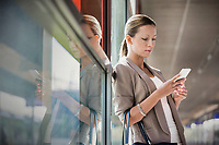 Portrait of young attractive businesswoman using smartphone while leaning on window