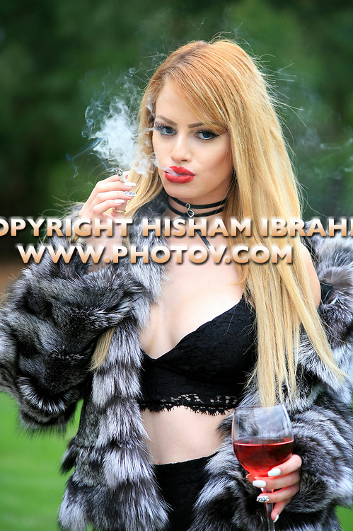 Glamorous young beautiful Latin woman in fur coat smoking cigarette.