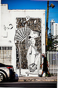 Man walks by a mural of a couple kissing, in Miami's Wynwood arts district