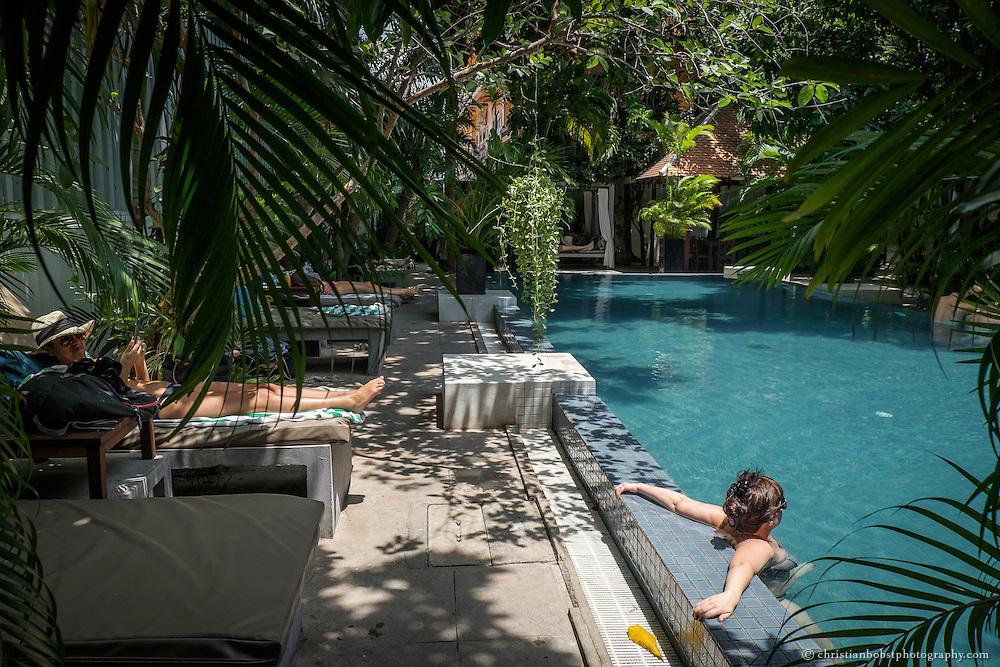 Gäste des Blue Lime Hotels in Phnom Penh entspannen sich unter Palmen und suchen im Pool Abkühlung von der dampfenden Hitze des heisstesten Monats Mai.