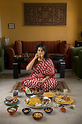 Millie Mitra, an education consultant and homeopathy devotee,  with her typical day's worth of food and a glass of urine at her home in Benson Town, Bangalore, India. (From the book  What I Eat: Around the World in 80 Diets.) The caloric value of her typical day's worth of food in December was 2100 kcals. She is 45 years of age; 5 feet, 1.5 inches tall; and 123 pounds.  Millie's quest for health includes yoga, a vegan diet, and topical applications of her own urine, as well as a daily glassful.  She has practiced Shivambu (sometimes spelled ?Sivambu?), which is the drinking of one's own first morning urine?200 cc in her practice?as a curative and preventative measure, for over 15 years. Millie applies urine to her skin as well, for the same reasons. Her husband Abhik has tried Shivambu and she helped her children to practice it when they were young, but currently only Millie practices urine therapy in her family. MODEL RELEASED.