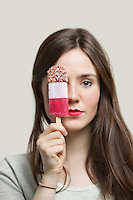 Portrait of young woman with red lips holding ice cream bar against gray background