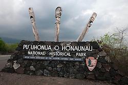 Entrance sign made of lava rock with Kapu Ki'i, wooden tiki statue carvings, made from the ohia tree, Pu'uhonua o Honaunau National Historical Park, The Big Island, Hawaii, United States of America