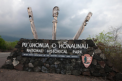 Entrance sign made of lava rock with Kapu Ki'i, wooden tiki statue carvings, made from the ohia tree, Pu'uhonua o Honaunau National Historical Park, The Big Island, Hawaii, United States of America