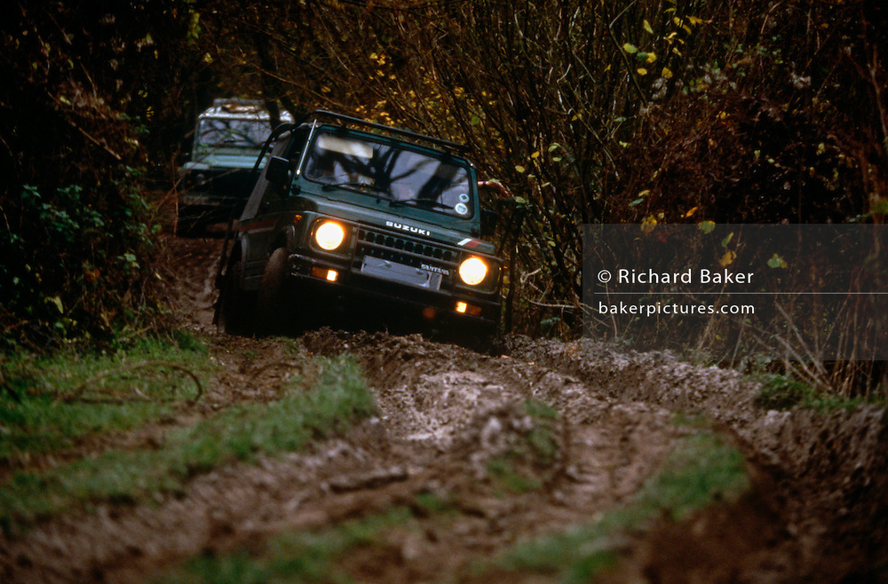 Followed by other vehicles, an anonymous Suzuki 4x4 drives along a boggy track in the English countryside. The drivers form a club of off-roaders who see it as their right to drive along public footpaths, designated as allowable for cars to drive upon. Churning up the mud, they create deep ruts in the path that disturbs local wildlife, alarms horses and endangers their riders if the world of technology meets nature. The front driver has taped over his registration plate number to remain unrecognisable.